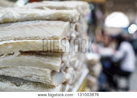 Photo of stand full of salty codfish fillet in the market, side view