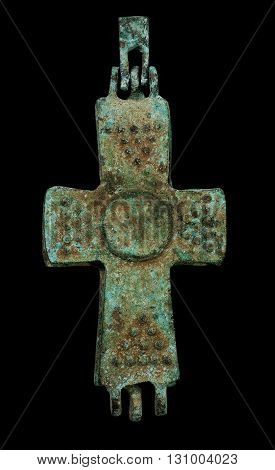 Ancient copper reliquary cross isolated on black closeup macro shot