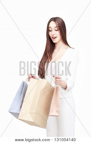 Happy young woman posing with shopping bags isolated on white background