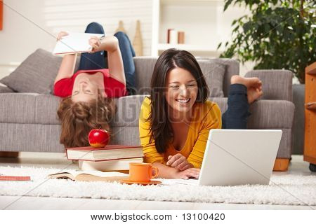 Happy teen girls studying at home in living room with books and laptop.