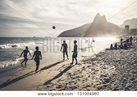 RIO DE JANEIRO BRAZIL - FEBRUARY 24 2015: A group of Brazilians playing on the shore of Ipanema Beach with the famous Dois Irmãos mountain behind them