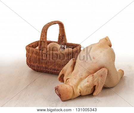 Raw chicken carcass home on the background basket with eggs on the kitchen table