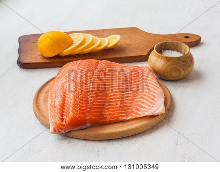 Fillet of red fish and lemon on a cutting board