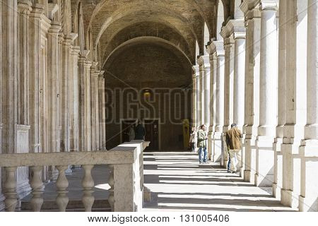 VICENZA-APRIL 3,2015:people on the famous colonnade of the Palladian basilica in the center of Vicenza during a sunny day.