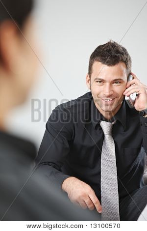Young Businessman sitting on Sofa in Büro-Lobby mit Palm-Organizer.