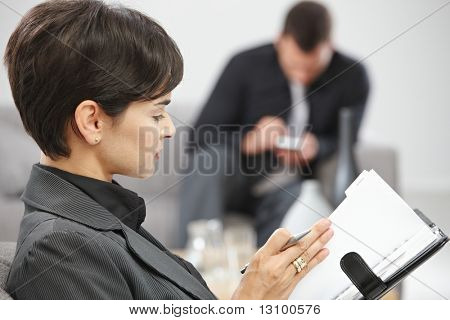 Young businesswoman sitting on sofe at office writing notes to personal organizer.