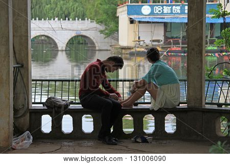 Girl And Boy Are Sitting On A Bench In Park, Kunming, China