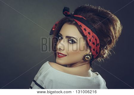Portrait of a beautiful smiling young fashion female model wearing white blouse red headband and retro updo hairstyle looking back over her shoulder against dark background.