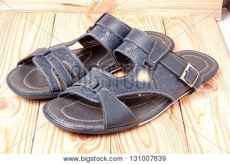 Men's summer sandals on a light wooden background.
