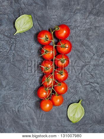 Tomatoes basil on a dark background. Vegetarian food healthy food concept. Top view. Flat lay. Organic food.