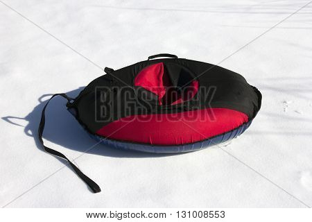 red and black material snow inner tubing (toobing) on the white snow