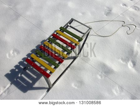 color wood and metal children sledges on the white snow
