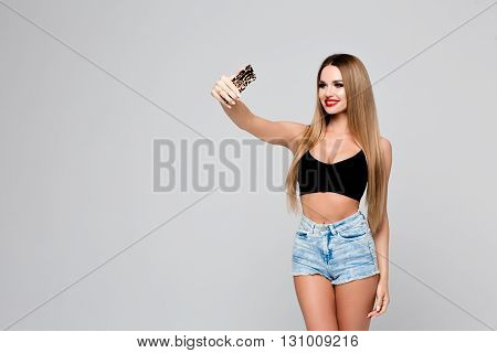 Beautiful young woman making selfie taking pictures of herself on the phone. Slender girl in a denim outfit with red lips makes a photo of herself on a smartphone