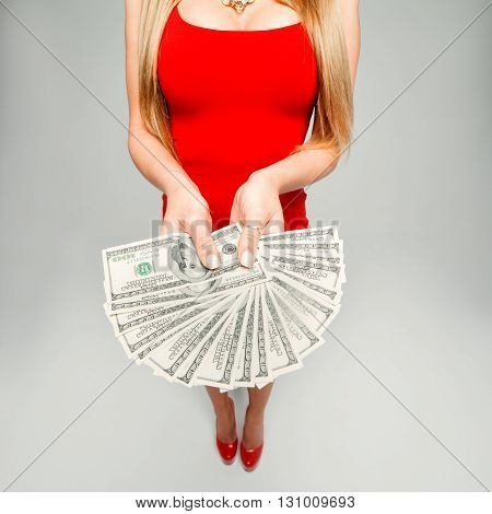 The girl holds in hands a lot of money. The woman in the red dress and red shoes with a fan of banknotes in his hands, his chest