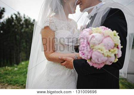 Close Up Portrait Of Beautiful Wedding Couple Under Veil With Peonies Wedding Bouquet In Hand