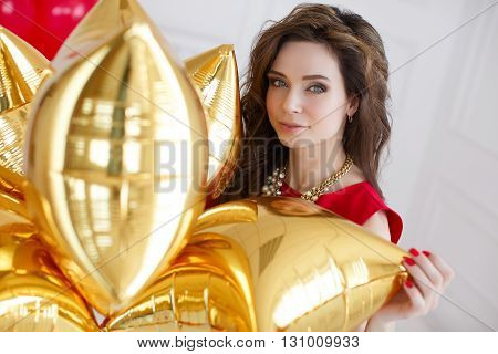 Young beautiful brunette woman with long curly hair and grey eyes,dressed in a red sleeveless dress,round neck wears a white necklace, a portrait, on light gray background in the Studio with a bunch of gold balloons - of pillows on your birthday