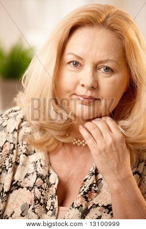 Porträt von Reife blonde Frau lächelnd in die Kamera, Hand aufgehalten zu Gesicht.