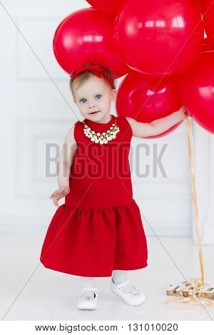 Beautiful little girl with blond hair and blue eyes, on his head a red bow,wearing a red sleeveless dress,round neck wears a large white necklace,Studio portrait with a bunch of red balloons on a light grey background