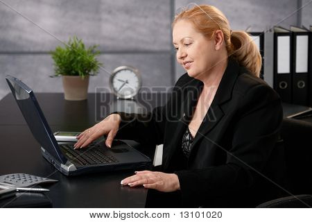 Senior businesswoman working on computer, typing on keyboard, looking at screen, smiling in office.