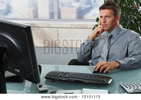 Confident businessman focusing on computer screen sitting at desk in office.