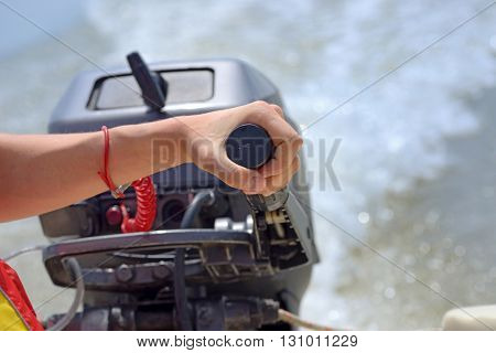 fisherman hand and speed boat engine, close up