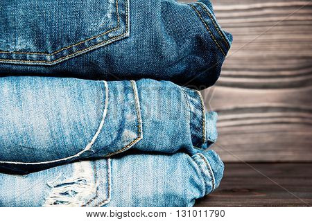 Pile of jeans clothes on a wooden background.