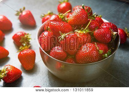 Fresh strawberries on dark ston background. Kitchen still life on table top.