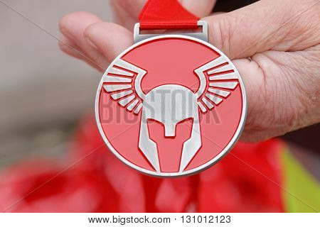 STOCKHOLM SWEDEN - MAY 14 2016: Hand holding the medal from the Tough Viking Event in Sweden April 14 2016