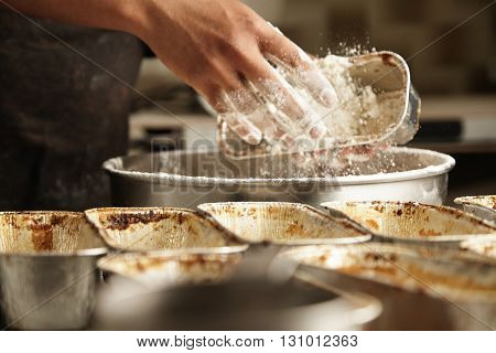 Close Focus On Hand Throws Flour Inside Cake Mold, Preparation Process Of Professional Baking In Art