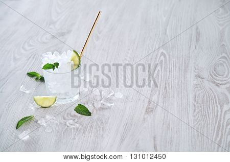 Isolated Whiskey Rox Glass Full Of Crashed Ice Cubes And Lime With Golden Drinking Straw On Wooden R