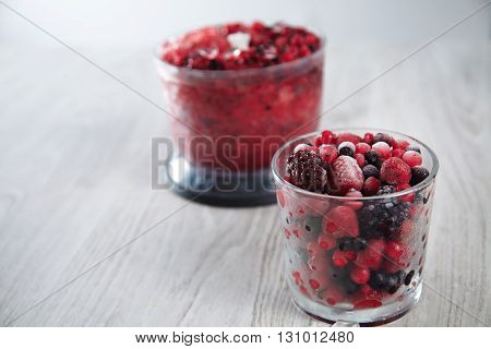 Mix Of Frozen Berries In Rox Glass In Front Of Unfocused Blender Pot With Blended Together Berries A