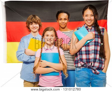 Four happy multiethnic teenage students standing against German flag, holding textbooks, isolated on white
