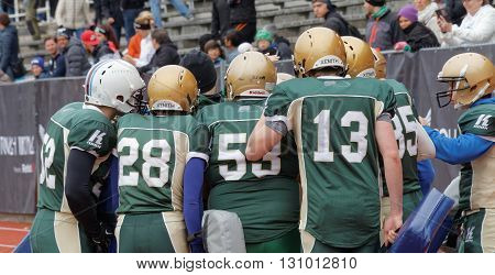 STOCKHOLM SWEDEN - MAY 14 2016: Football players wearing golden helmets discussing they are the first obstarcle in the obstacle race Tough Viking Event in Sweden April 14 2016