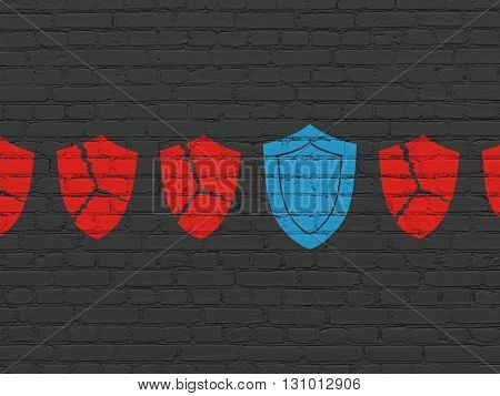 Safety concept: row of Painted red broken shield icons around blue shield icon on Black Brick wall background
