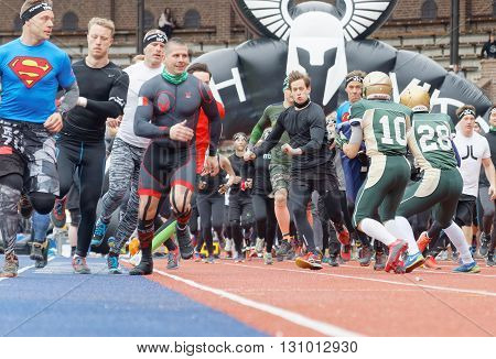 STOCKHOLM SWEDEN - MAY 14 2016: Lots of runner trying to pass the first obstracle american football players after the start in the obstacle race Tough Viking Event in Sweden April 14 2016