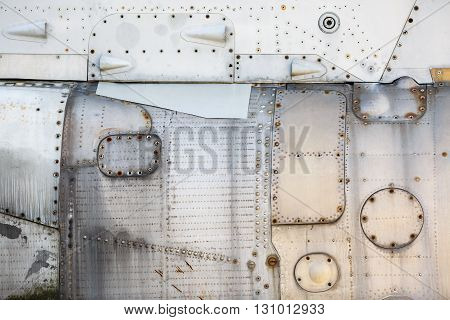 Vintage metal texture. Weathered metallic background. Old vintage metal background with rivets and bolts. Sheathing old airplane.