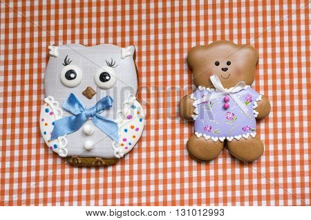 A cute vichy background with a handmade honey-cake bear and a handmade honey-cake owl  for a baby shower party, a birthday party or other events.