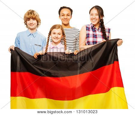 Picture of four smiling teenage kids holding German flag, standing behind it, isolated on white