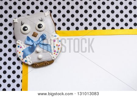 A cute polka dot background with a handmade honey-cake owl  and a ribbon and a place for your text for a baby shower party, a birthday party or other events.
