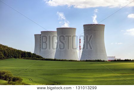 Nuclear power plant with green field at day