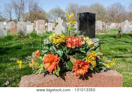 Flowers on a tombstone in a cemetary with hundreds of tombstones in the background