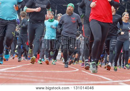 STOCKHOLM SWEDEN - MAY 14 2016: Running feet and legs and a man with beard after the start in the obstacle race Tough Viking Event in Sweden April 14 2016
