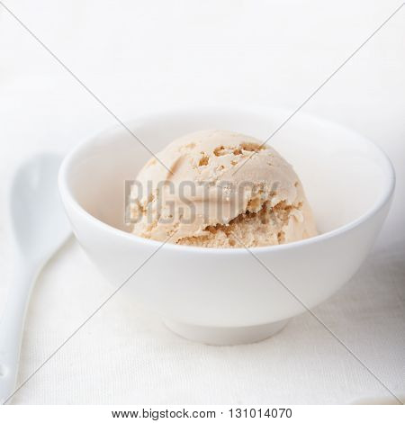 Ice cream with Earl grey tea flavor in white ceramic bowl on a white textile background Homemade Organic product