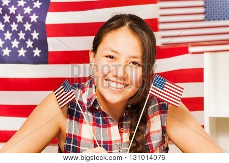 Smiling teenage Asian girl with two flags of United states of America