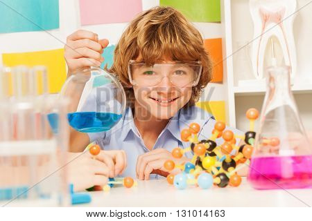 Young boy in safety goggles holding flask with blue reagent at the chemical laboratory