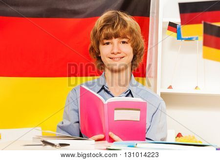 Smiling teenage boy with textbook and the colors of German flag behind