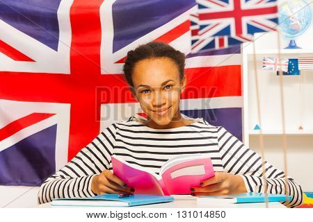 Beautiful African student in frock reading textbook at the class, sitting against the flag of Great Britain