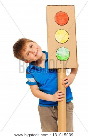 Smiling boy emerging from behind handmade model of cardboard lights, isolated on white background