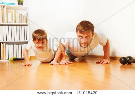 Father and son working out together, doing pushups at home