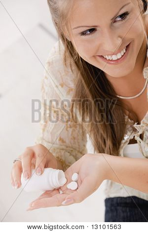 Portrait of young woman girl taking pills from bottle, smiling.